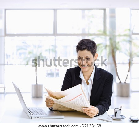 Happy businesswoman sitting at table in office lobby, reading newspaper, using laptop computer.