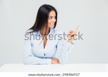 Happy businesswoman sitting at the table and pointing finger away over gray background #298486937