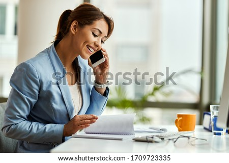 Happy businesswoman talking on mobile phone while analyzing weekly schedule in her notebook.