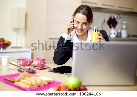 Happy businesswoman talking on the phone during breakfast at home in the morning
