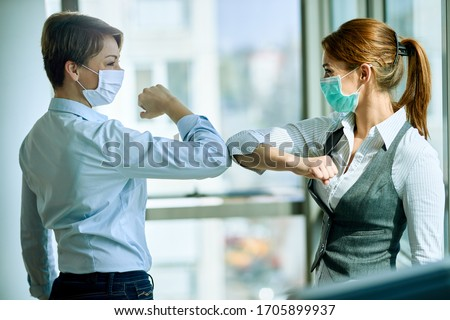 Happy businesswoman wearing face masks and elbow bumping while meeting in the office during coronavirus epidemic.