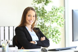 Happy businesswoman wearing suit posing sitting looking at camera at office