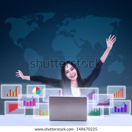 Happy businesswoman with arm raised looking at bar graphs