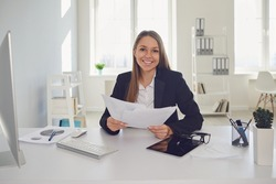 Happy businesswoman with documents in hands sitting at table