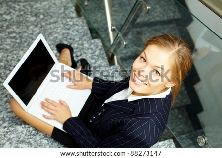 Happy businesswoman with laptop looking at camera while working on staircase