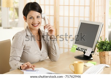 Happy businesswoman working at desk in office, talking on phone, using calculator. Copyspace on screen.