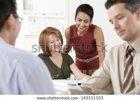 Happy businesswomen at desk with male colleagues in foreground