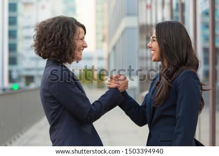 Happy businesswomen celebrating team success. Business ladies giving friendly handshake. Corporate success concept #1503394940