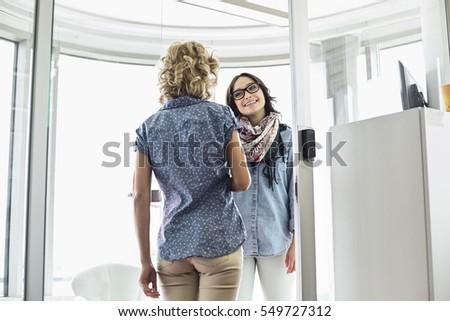 Happy businesswomen conversing in creative office #549727312