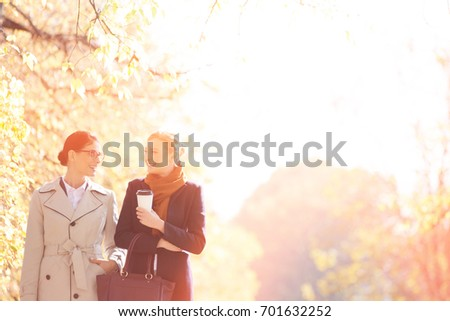 Happy businesswomen conversing while walking at park on sunny day #701632252