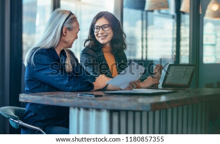 Happy businesswomen having a meeting in office. Two business colleagues discussing business matters. #1180857355