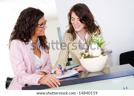 Happy businesswomen working together in team at office reception, looking at documents, talking, smiling.