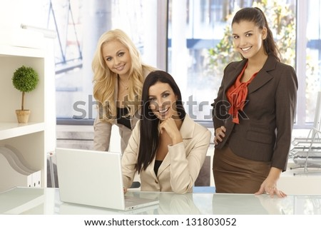 Happy businesswomen working together on computer at desk looking at camera, smiling. - stock photo
