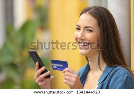 Happy buyer buys on line with credit card and smart phone and looks at you in the street