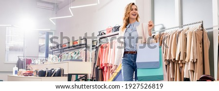 Happy byer with shopping bags standing in showroom, banner