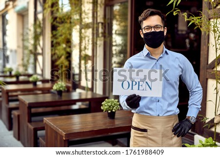 Happy cafe owner holding open sign while wearing protective face mask and gloves.