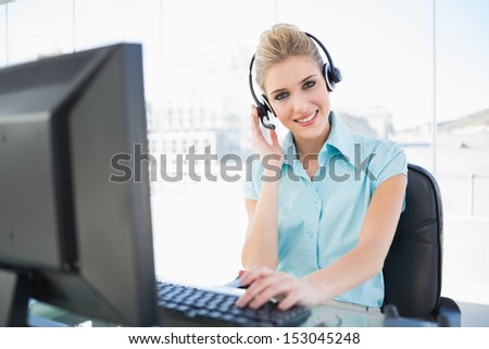 Happy call center agent working on computer in bright office