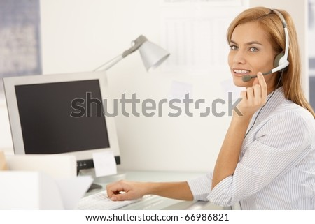 Happy call center worker girl sitting at desk in office, using desktop computer with headset, smiling.?