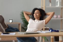 Happy calm african girl student relaxing holding hands behind finished study work breathing fresh air sit at home office desk feel stress relief stretching doing exercise dreaming enjoy peace of mind