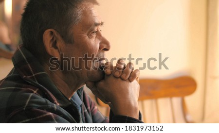 Happy calm relaxed senior man sitting at dinner table at home, looking ahead, thinking. Portrait, closeup Stockfoto ©