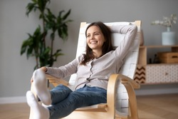 Happy calm young woman relaxing on comfortable wooden rocking chair in living room, smiling millennial girl having fun resting in armchair at home feeling stress free enjoying healthy weekend