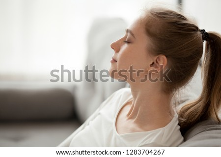 Happy calm young woman relaxing with eyes closed breathing fresh air dreaming on couch, healthy girl resting on sofa thinking enjoying peaceful mood feeling relief, lounge at home, peace of mind #1283704267