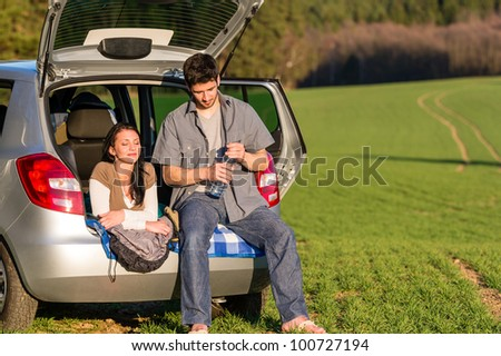 Happy camping couple lying inside car summer sunset countryside - stock photo