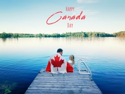 Happy Canada Day. Holiday card with text. Father and daughter wrapped in large Canadian flag sitting on wooden pier by lake in countryside. Canada Day celebration outdoor.