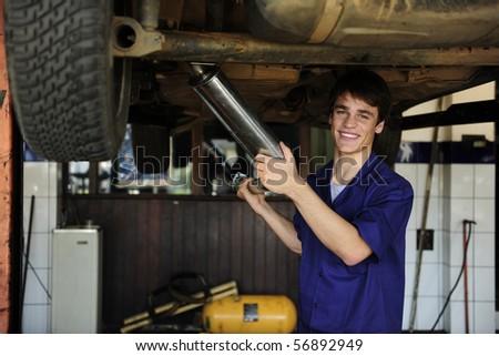 happy car mechanic working at the car  repair  shop
