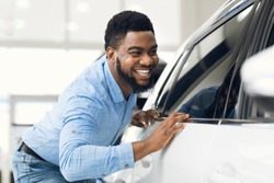 Happy Car Owner. African Guy Touching His New Vehicle Excited About Buying Automobile In Dealership Showroom. Selective Focus