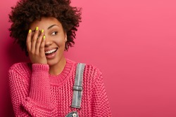 Happy carefree ethnic woman makes face palm, looks happily, hears something hilarious, wears warm jumper, expresses positive emotions, isolated on bright pink background, copy place for promotion