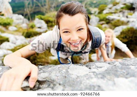 happy carefree hiking backpacker climbs a rock outdoors while leading a healthy lifestyle - stock photo