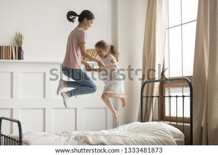 Happy carefree mom baby sitter and cute kid girl holding hands jumping on bed together, family mother playing having fun with little child daughter laughing feeling joy fly in air at home in bedroom