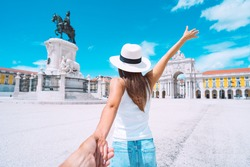 Happy carefree tourist woman in white hat leading her boyfriend and enjoying sunny summer holiday. Follow me. Couple on vacation. Traveling together. Commerce Square in Lisbon, Portugal.