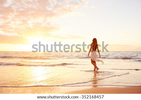 Happy Carefree Woman Enjoying Beautiful Sunset on the Beach #352168457