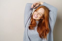 Happy carefree young redhead woman with a cute grin posing with her hands over her head and eyes closed on a studio background with copy space