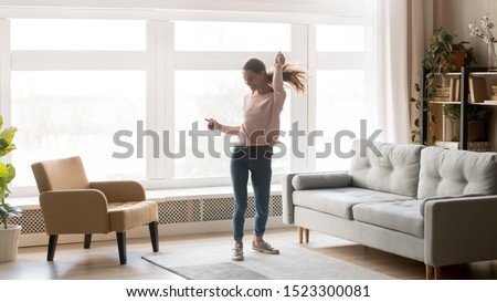 Happy carefree young woman dancing alone having fun at home listening to good music, energetic girl moving jumping in modern living room interior with large window enjoy freedom and active lifestyle