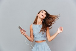Happy carefree young woman dancing and listening to music from smartphone over grey background