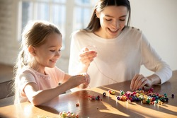 Happy caring young Caucasian mother and little 6s daughter have fun together making bracelets string colorful beads on thread. Smiling mom and small girl child involved in funny hobby activity.