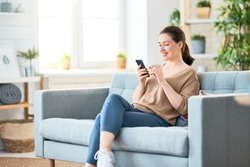 Happy casual beautiful woman is talking on a phone sitting on a sofa at home.
