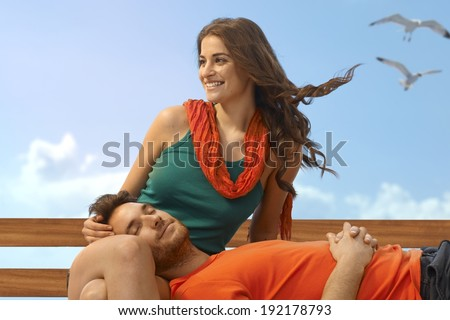 Happy casual caucasian handsome man sleeping in lap of attractive girlfriend at beach. Smiling couple, sitting, wind blowing, summer holiday relaxation. Copyspace.