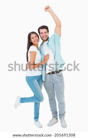 Happy casual couple cheering at camera on white background