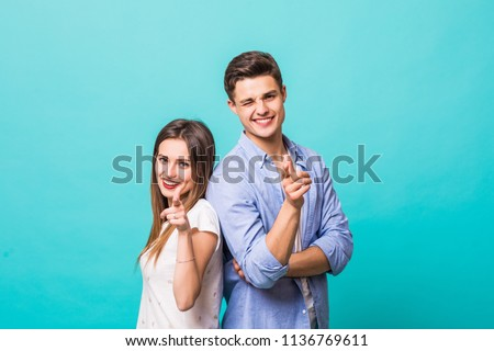 Happy casual couple inviting you to something, presenting and pointing finger on white background #1136769611