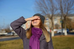 Happy casual excited woman celebrating success. stands on the street warmly dressed in a gray hat and a purple. covered her eyes with her hand with happiness or hides her eyes from the bright sun