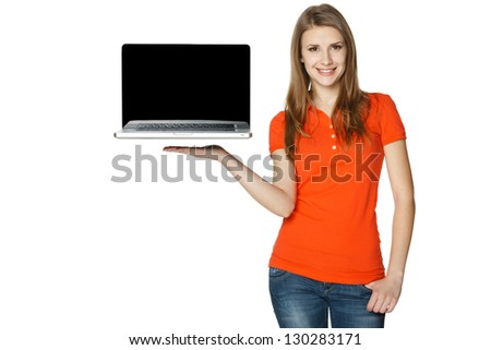 Happy casual female showing a laptop screen, isolated over a white background