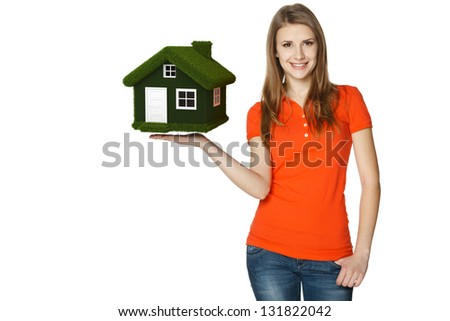 Happy casual female showing eco house, isolated over a white background