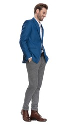 Happy casual man holding his hand in his pockets and smiling while looking down and wearing a suit, posing on white studio background