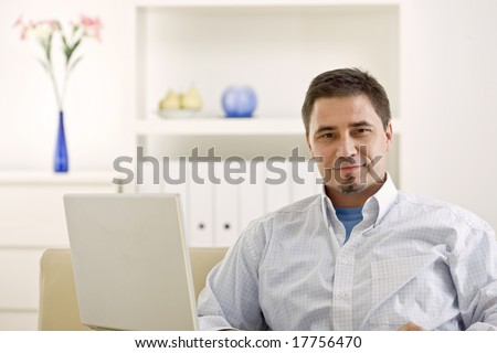 Happy casual man teleworking using laptop computer at home. - stock photo