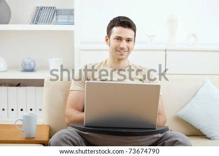 Happy casual man using laptop computer at home, sitting on couch, looking at camera, smiling.?