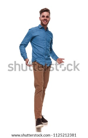 happy casual man wearing a blue shirt standing on white background and presenting, full length picture #1125212381